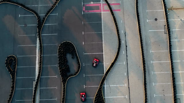 Aerial drone view of racing go karts Aerial drone view of go karts racing on racing track go cart stock videos & royalty-free footage