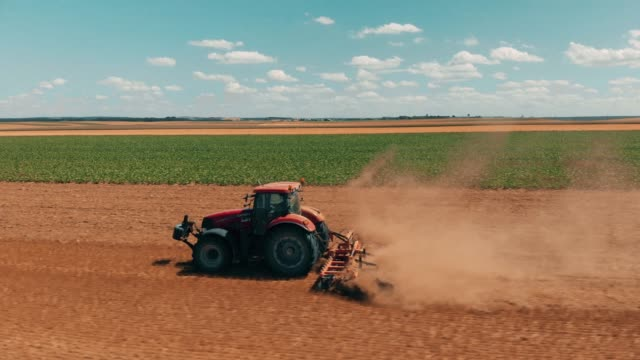 Aerial drone view of red tracor working in wheat field. Agriculture and environment in European Union.