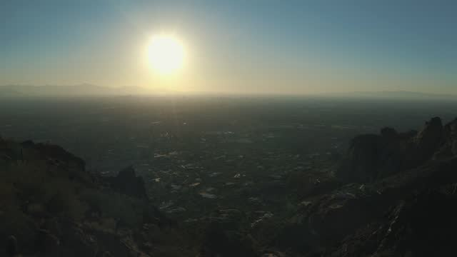 Aerial Drone View of Scottsdale, Tempe and Camelback East Village in Arizona from Camelback mountain during golden hour on a bright afternoon with blue sky