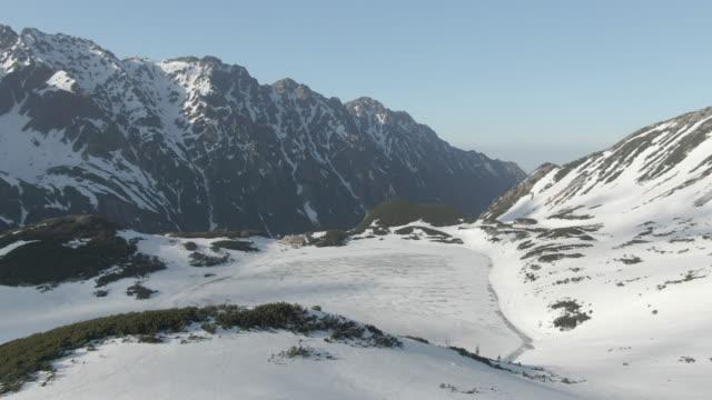 stockvideo's en b-roll-footage met luchtfoto drone uitzicht op besneeuwde bergen - sneeuwkap