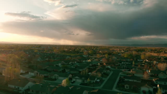 Aerial Drone View Of Subdivisions In The Grand Valley At Sunset, Snowy Grand Mesa, Book Cliffs