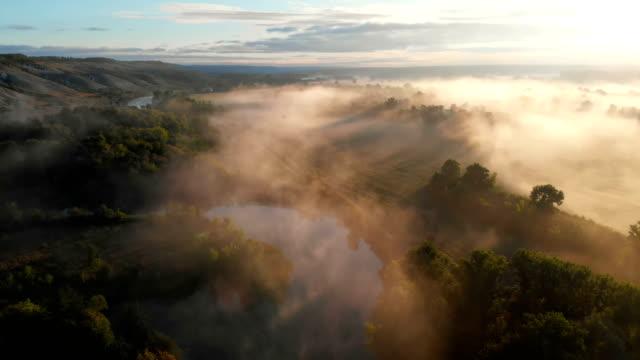 vídeos de stock e filmes b-roll de aerial drone view of sunrise over misty river - budismo