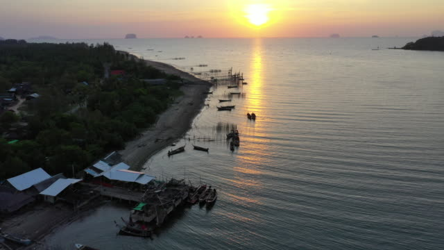 Aerial drone view of sunset over a shallow, tropical ocean with traditional wooden longtail boats at anchor, Southern of Thailand