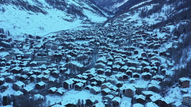 stockvideo's en b-roll-footage met luchtfoto drone uitzicht op de stad van zermatt bedekt met sneeuw in de schaduw - zermatt