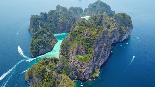 aerial drone view of tropical maya bay and limestone cliffs, phi phi islands, thailand - wyspa land feature filmów i materiałów b-roll