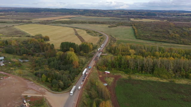 Aerial drone view road repair work and meadow landscape. Trucks on road driving away in beautiful countryside with green grass in Direction of Loading Warehouse Area. - vídeo