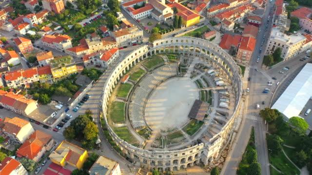 aerial drone view sunset scene of pula arena, a roman amphitheatre with adriatic sea in pula. istria, croatia - хорватия стоковые видео и кадры b-roll