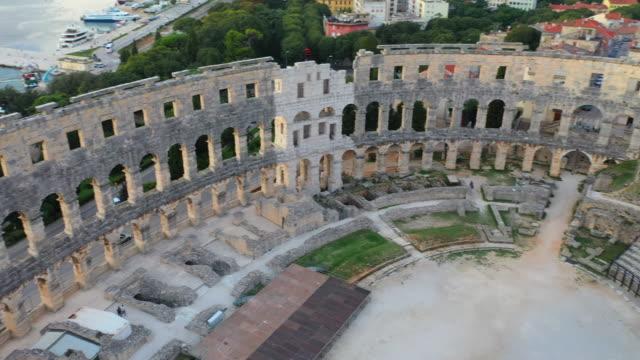 Aerial Drone view Sunset Scene of Pula Arena, A Roman Amphitheatre with Adriatic Sea in Pula. Istria, Croatia