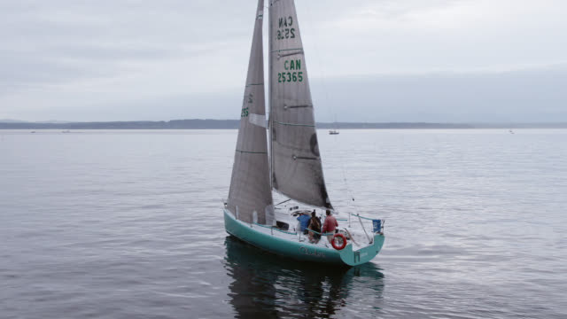 Aerial Drone/Dolly Shot of a Sailboat with a Small Crew Heading Out into the Puget Sound in Washington on an Overcast Day