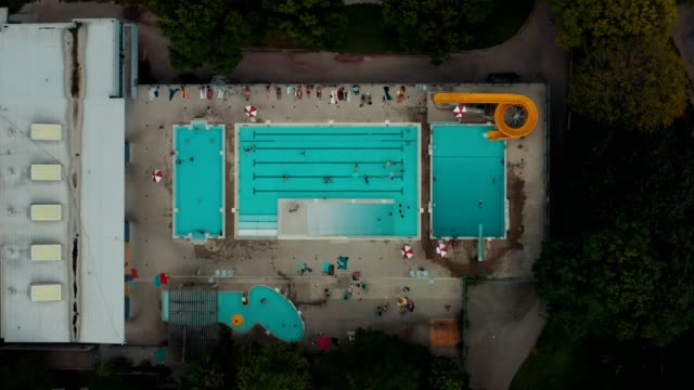 Aerial establishing shot of a public pool in a large city. Aerial establishing shot of a public pool in a large city. Cinematic 4K footage. pool party stock videos & royalty-free footage