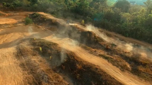 Aerial: Fast riding and jumping on motocross bike.