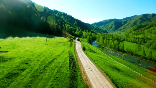 Aerial FHD FullHD view. Low air flight over mountain rural dirt road and meadow video
