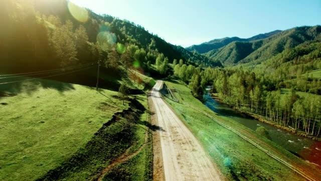 fhd fullhd 空撮。山農村未舗装の道路と晴れた夏の朝に草原上低空気飛行。近くには緑の木々、太陽光線、山川 - 川岸点の映像素材/bロール