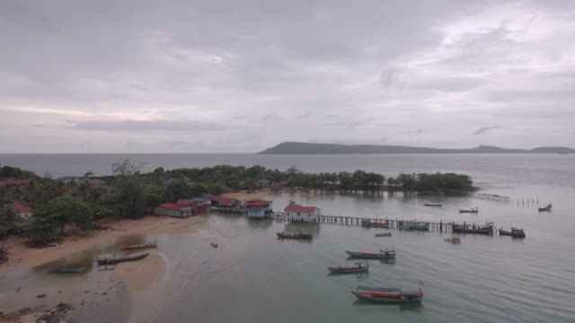 Aerial : fishing village and wooden pier on the sea bay video