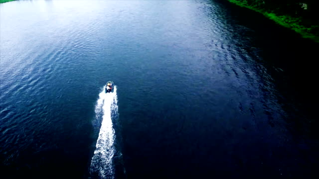 Aerial flight bird view catching up motorboat moving fast over quiet river video