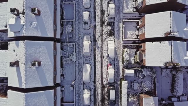 Aerial flight down a traditional UK terraced house street that's covered in snow after a blizzard the night before.