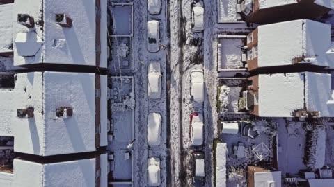 vidéos et rushes de vol aérien vers le bas un uk traditionnelle mitoyenne rue de maison qui est couverte de neige après une tempête de neige la nuit précédente. - hiver