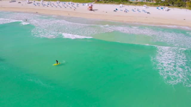 Aerial flight Miami Beach waves and surfboarders