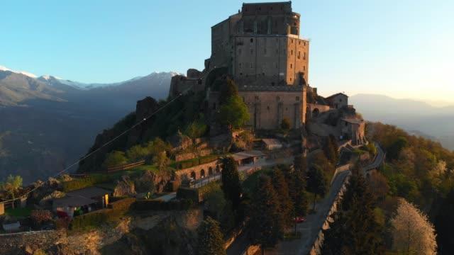 vídeos de stock, filmes e b-roll de aéreo: voo sobre antiga abadia medieval empoleirado no topo de uma montanha - turim, itália - castelo