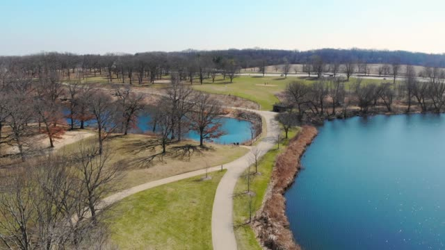 vídeos de stock e filmes b-roll de aerial flight over the fabulous park in the state of illinois usa. park areas in the united states. fall or spring. spring park from a height - margem do lago