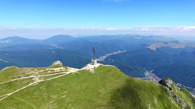 Aerial flight over the Heroes Cross on Caraiman Peak, Romania, tilt video