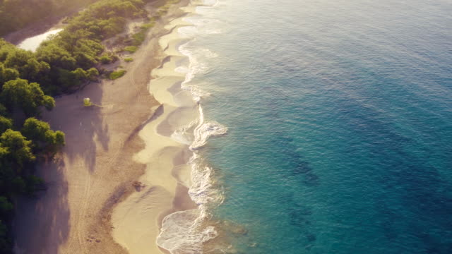4K Aerial Flight Over White Sandy Beach and Beautiful Blue Ocean. Amazing Sunrise Over Tropical Landscape.