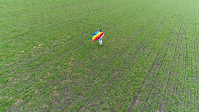 Aerial flight over woman with pride flag video