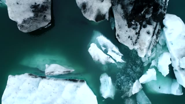 vídeos de stock e filmes b-roll de aerial flight with drone over the of icebergs floating in jokulsarlon lagoon by the southern coast of iceland - iceberg