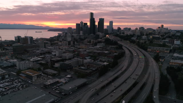 Aerial Floating Over City with Sunset Colors on Ocean Water and Mountain Range video