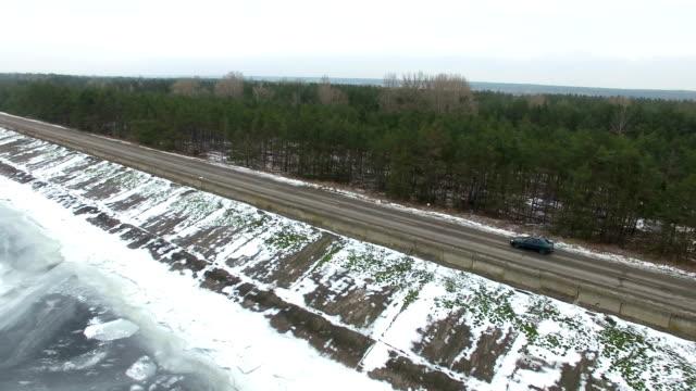 4k空中。凍った海と木材の近くの冬の道路で一人で車を飛び回る - 陸の乗り物点の映像素材/bロール