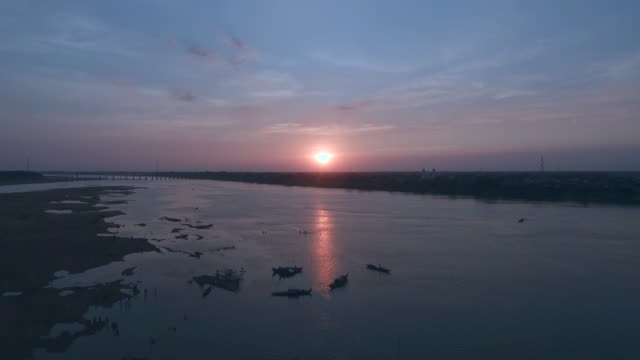 aerial: fly back revealing a bamboo bridge over river at sunset , with silhouettes of people swimming around aerial : fly back revealing a bamboo bridge over river at sunset, with silhouettes of people swimming around back to back stock videos & royalty-free footage