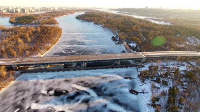 4K Aerial. Fly over frozen winter river and bridge in city suburb. Lateral flight