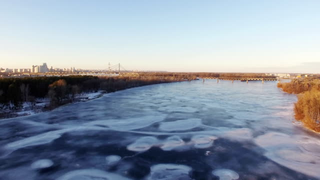 4K Aerial. Fly over frozen winter river in city, sunny day.