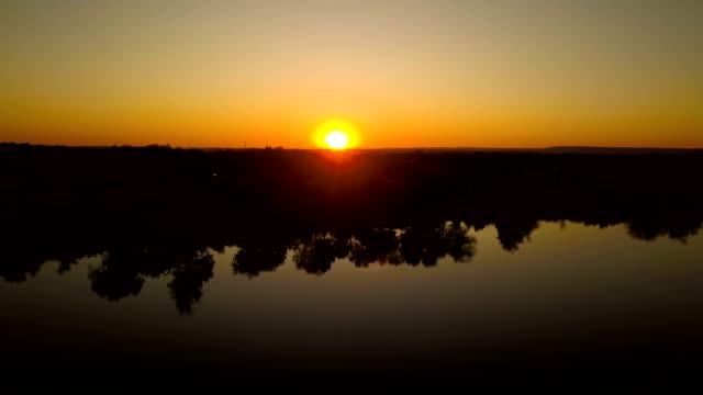 4k空中。 木々の反射で日没や日の出の湖の上を飛びます。風景 - コントロール点の映像素材/bロール