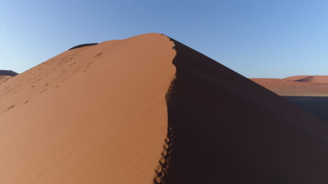 Aerial fly over view of male Tourist walking up a sand dune in the Namib desert video
