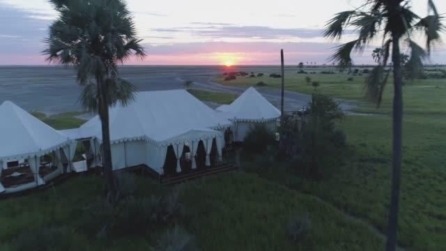 vidéos et rushes de survol aérien 4k sur la zone de réception de san camp, sur les pans de makgadikgadi, botswana - lieu sportif
