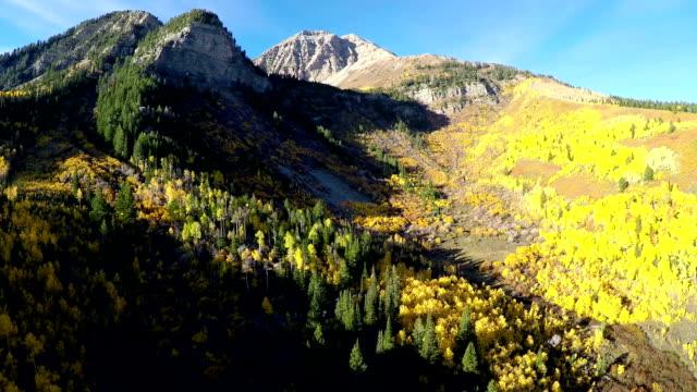 aerial fly towards mountain peaks with fall colors - klippiga bergen bildbanksvideor och videomaterial från bakom kulisserna