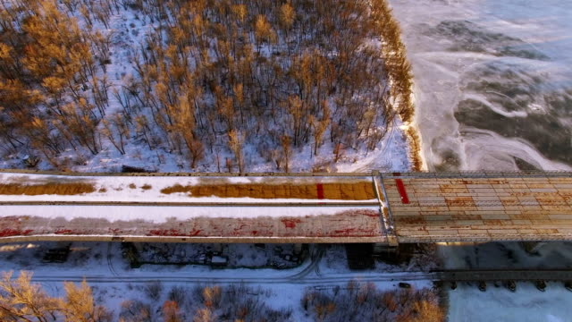 4K Aerial. Fly with camera inclination over frozen winter river and bridge