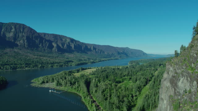 Aerial flyby moving right of Beacon Rock and the Columbia River on a blue sky sunny day video