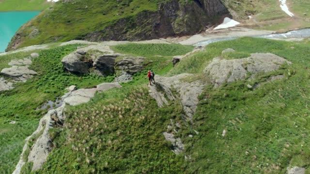 antenne: herumfliegen paar wanderer auf berggipfel - panorama stock-videos und b-roll-filmmaterial
