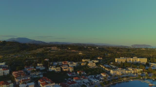 Aerial - flying backwards above a small harbor at dusk - Porto Heli - Porto Cheli - Greece - Argolis - Argolida video