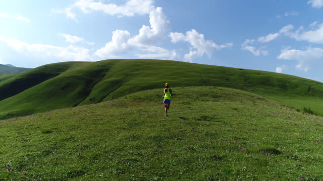 aerial flying drone  view of young fitness woman trail runner running on top of  grassland mountain aerial flying drone  view of young fitness woman trail runner running on top of  grassland mountain grass area stock videos & royalty-free footage