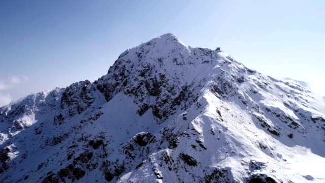 aerial flying moving backward over snowy mountain peak ridge establisher. Outdoor snow alpine wild nature scape in winter. 4k drone flight establishing shot aerial flying moving forward over snowy mountain peak ridge establisher. Outdoor snow alpine wild nature scape in winter. 4k drone flight establishing shot snowcapped mountain stock videos & royalty-free footage
