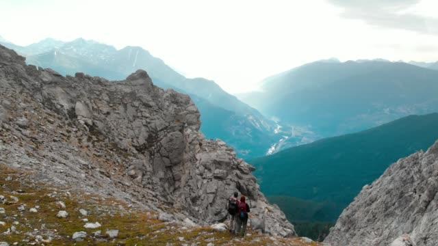 antenne: überfliegen paar wanderer auf berggipfel - panorama stock-videos und b-roll-filmmaterial
