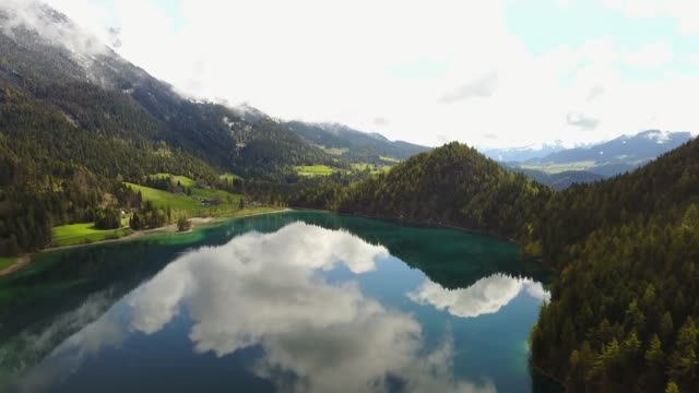 aerial: flying over hintersteiner mountain lake with clear water in austria - stato federato del tirolo video stock e b–roll