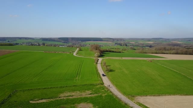 aerial: flying over the agrarian hilly fields in somme-leuze in belgian ardennes - belgio video stock e b–roll