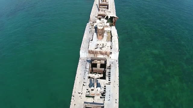 Aerial flying over the shipwreck Evangelia , showing advanced structural damage of the upper deck and entire vessel , stranded on the Black Sea coast , Romania video