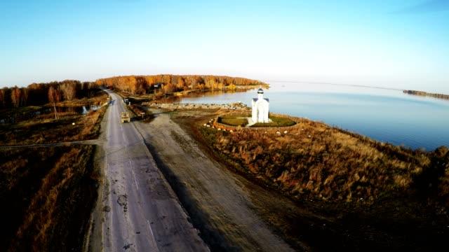 aerial flying over the small church by the lake - jesus christ filmów i materiałów b-roll