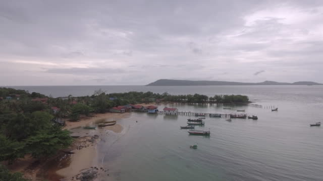 Aerial : flying slowly towards fishing village and wooden pier on the sea bay video