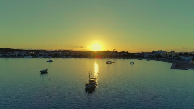 Aerial - flying straight forward above a small harbor at dusk - Porto Heli - Porto Cheli - Greece - Argolis - Argolida video